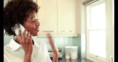 Happy woman in her kitchen on the phone video