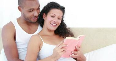 Pregnant woman and her husband reading a book video
