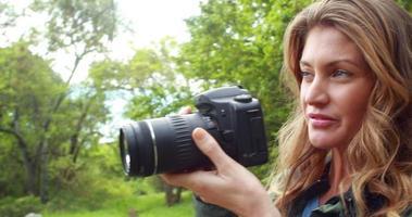 donna sorridente durante un'escursione scattare una foto video