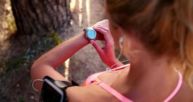 mulher corredora verificando seu tempo de corrida no relógio esportivo