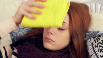 kranke Frau mit nassem Handtuch auf der Stirn. Kompresse
