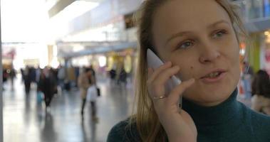 Frau telefoniert am Bahnhof