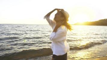 mujer feliz bailando en la playa al atardecer