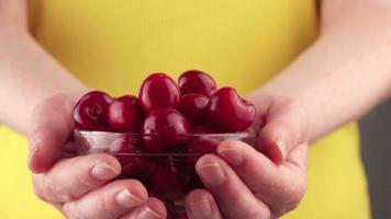 mujer sosteniendo un cuenco con cerezas maduras