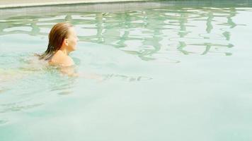 Frau schwimmt in einem Pool und steigt dann aus