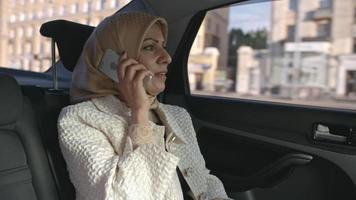 donna araba che risponde al telefono sul sedile posteriore della macchina