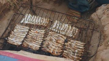 Frau, die Grillfisch auf eingegrabenem Grill mit Pappe bedeckt