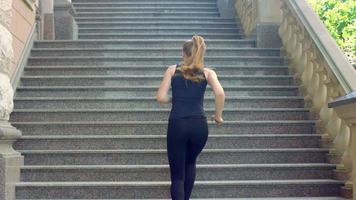 donna correre su per le scale al rallentatore. esercizio di perdita di peso