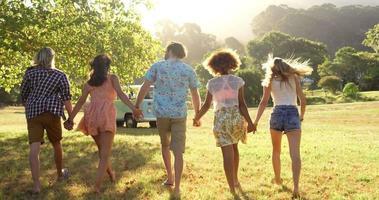 retrovisor de amigos hipster de mãos dadas e caminhando
