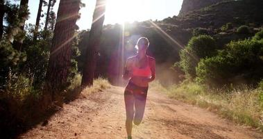 Athletic woman running on a mountain nature trail with sunflare video