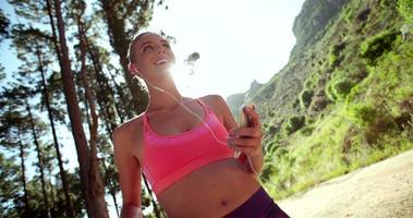 Healthy woman using phone while outdoors ready for a run