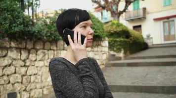 Porträtfrau, die auf dem Handy in der Landschaft spricht