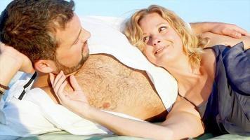 Mann gibt einer Frau spielerisch eine Rose am Strand