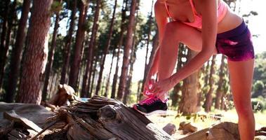 Frau Trailrunnerin fixiert ihre Schnürsenkel an ihren Laufschuhen