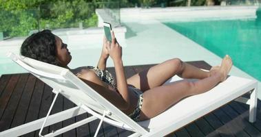 attraktive Frau, die auf Liegestuhl mit Smartphone liegt