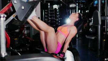 Athletic woman trains muscles of the legs in the gym video