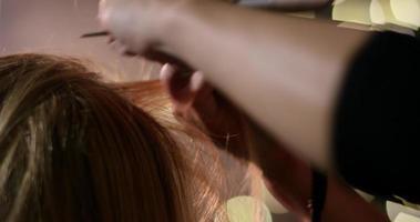 Frau lässt sich von einem professionellen Visagisten die Haare machen.