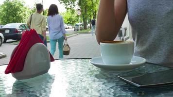 Woman drinking coffee on cafe. Glasses are nearby the cup video