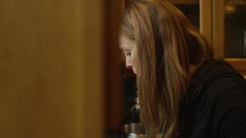 uma mulher lavando uma tigela na pia da cozinha