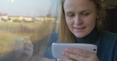 Mujer en tren usando celular y mirando por la ventana