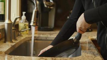 uma mulher esfregando uma panela na pia da cozinha em casa