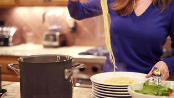 Une femme servant des nouilles spaghetti chaudes sur des assiettes dans une cuisine