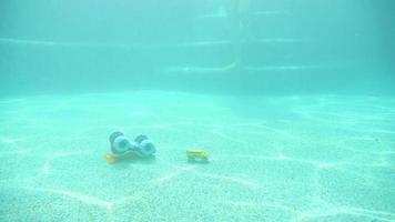 femme trébuche sur des jouets marchant au fond d'une piscine