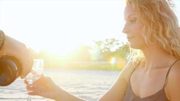 donna che beve un bicchiere di vino sulla spiaggia al sunsest