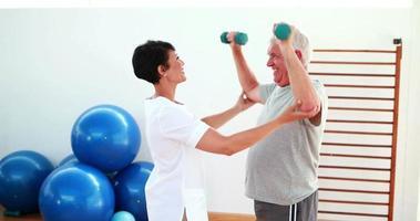 Linda fisioterapeuta ajudando paciente idosa a levantar pesos nas mãos
