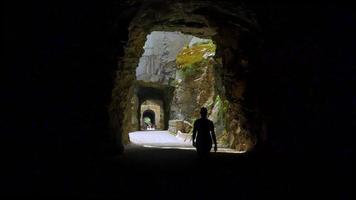 túneis de trem abandonados, mulher caminhando da escuridão para a luz, ferrovia dos anos 1800