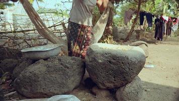 Mujer golpeando los alimentos con un mortero con mango en un mortero de piedra video