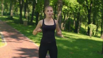 mulher de aptidão aquece os ombros ao ar livre. garota apta se alongando no parque verde