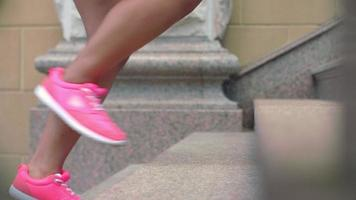 Legs of fitness woman and man in sport shoes walking up steps