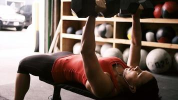 A fit young woman doing a dumbbell bench press dans une petite salle de sport
