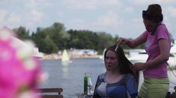 meisje in roze overhemd kapsel maken jonge vrouw. terras aan zee. zomer