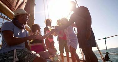 gruppo di amici che tostano con bevande su uno yacht