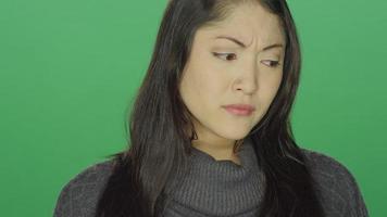 Hermosa joven asiática comenzando a llorar, sobre un fondo de estudio de pantalla verde