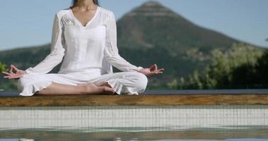 ruhige Frau, die Yoga am Pool macht