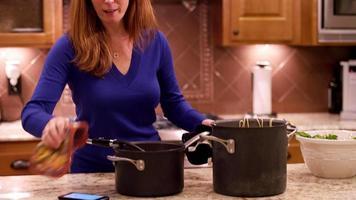 Eine Frau stellt einen heißen Topf auf eine Theke mit Topflappen video