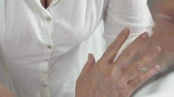la massaggiatrice fa un massaggio medicinale della mano destra alla donna adulta nel salone di bellezza
