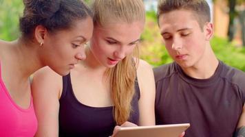 gli amici leggono notizie scioccate nel tablet. facce scioccate. amici multirazziali scioccati