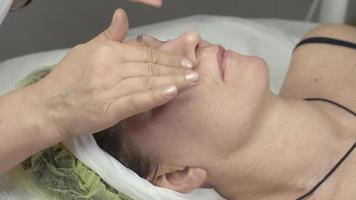 cosmetologista colocou óleo umidificador no rosto de uma mulher adulta com as mãos em um salão de beleza