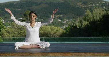 donna calma facendo yoga a bordo piscina