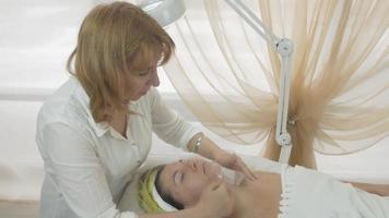 Die Kosmetikerin hat im Schönheitssalon etwas feuchtigkeitsspendendes Öl auf Gesicht und Hals der Frau aufgetragen