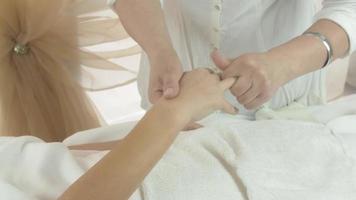 la massaggiatrice fa il massaggio di ogni dito sulla mano destra della donna nel salone di bellezza