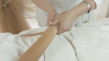 massaggiatrice fa il massaggio delle dita, palmo sulla mano destra della donna nel salone di bellezza