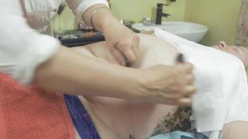 la massaggiatrice fa il massaggio della terapia con pietre dello stomaco alla donna grassa nel salone. accarezzando