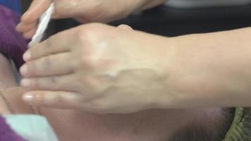 cosmetologo pulire il viso di donna spessa nel salone di bellezza eliminando un batuffolo di cotone