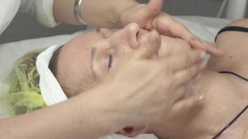 cosmetologista esfregaço umidificador de óleo no rosto de uma mulher adulta com as mãos em um salão de beleza