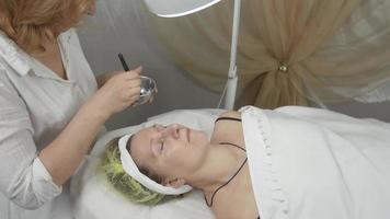 Kosmetikerin legte Wasser auf erwachsene Frau Gesicht durch Pinsel in Schönheitssalon. Reinigung